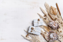 Gifts Decorated By Dried Flowers And Grasses; Pampas Grass, Gold Painted Palm Fronds, Bulrush, Ruscus Leaves, King Protea, Australian Banksia And Gold Painted Gum Nuts, On A Rustic White Background.