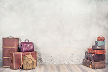 Vintage Classic Outdated Trunks Luggage, Old Antique Leather Suitcases, Backpacks Front Concrete Wall Background. Travel Baggage Concept. Retro Style Filtered Photo