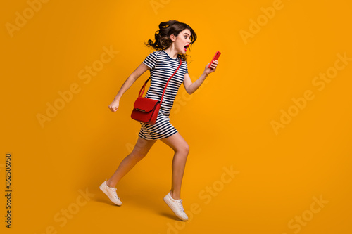 Fototapeta I'm late Full body profile photo of crazy lady rush work check time telephone hurry speed open mouth wear casual striped mini dress clutch shoes isolated yellow color background obraz