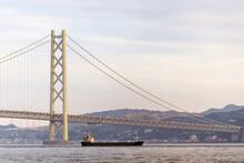 Cargo Ship Cruising Under Suspension Bridge At Sunset