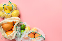 Fruits And Citrics In Reusable Eco-friendly Mesh Bags On Pink Background. Zero Waste Shopping.