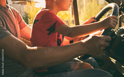 Fototapeta The child is sitting on the father's knees in the car and learning how to drive the car obraz