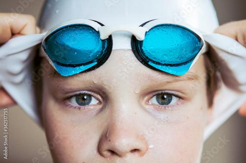Fototapeta Portrait of a swimmer boy in a hat and glasses