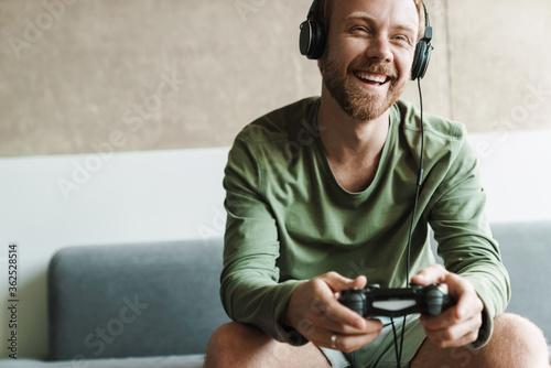 Fototapeta Photo of man playing video game with joystick while sitting on sofa obraz