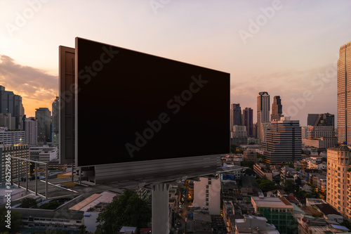 Blank black road billboard with Bangkok cityscape background at sunset Canvas Print