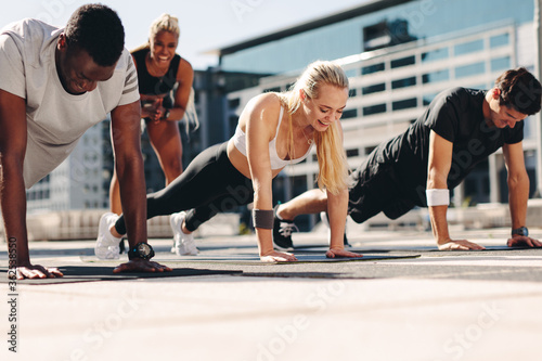 Group of people doing push ups outdoors Fototapeta