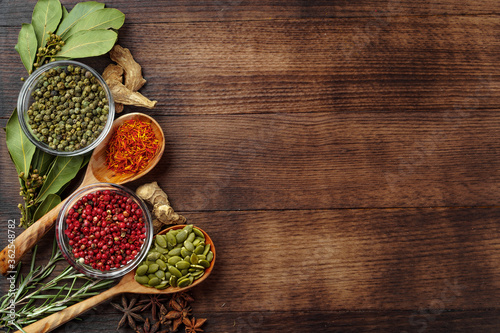 Fotografie, Obraz Vivid colorful spices in wooden spoons on wooden background