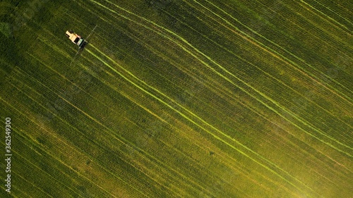 Fotografija Birds-eye view of a tractor working in a green field