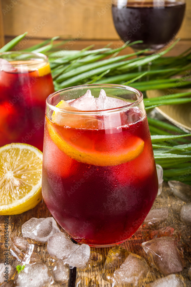 Fototapeta Tinto de Verano or vino de verano, Spanish Wine Cocktail. Refreshment acoholic drink sangria. Cool iced alcohol beverage with lemon juice and slices, wooden background with summer tropical decor copy