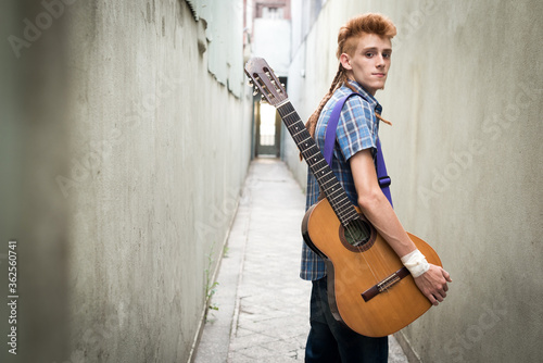 Slika na platnu Portrait Of Young Man With Guitar Walking On Alley Amidst Wall