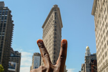 Flatiron Building - Low Angle View Of Hand Holding Built Structure Against Sky