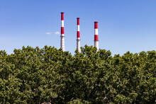 Three Tall Smoke Stacks With Green Trees And A Blue Sky
