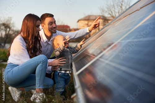 Photo Side view shot of a young modern family with a little son getting acquainted wit