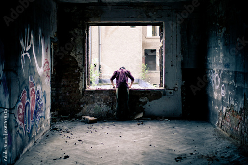 Young Man Looking Out Of The Window Of An Old Factory In Leipzig, Germany Fototapet