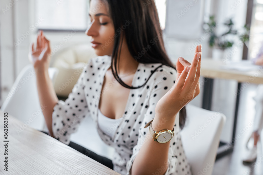 Fototapeta selective focus of beautiful businesswoman with closed eyes meditating in office