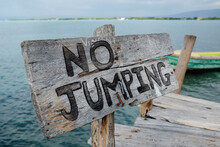 Wooden No Jumping Sign On Wooden Boardwalk