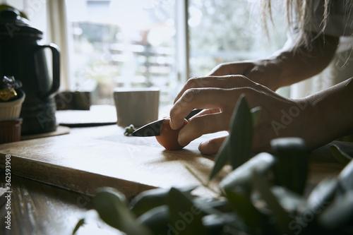 窓辺で包丁でトマトをカットして料理する女性の手