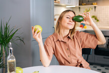 Attractive Woman Sitting At Table And Holding Of Green Tasty Avocado In Front Of Eyes In Kitchen With Modern Interior. Girl Holding Apple In Hand. Concept Of Healthy Eating.
