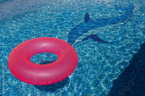 Photo Flotador rosa flotando en el agua cristalina de una piscina azul con un delfín e