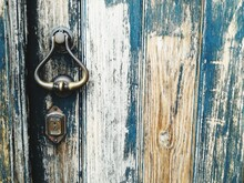 Close-up Of Door Knocker On Weathered Wood