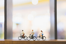 Figurines On Bicycles Over Wood