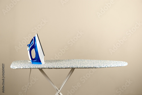 Homework. Blue electric iron on ironing board Canvas