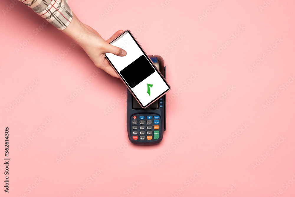Fototapeta Woman paying by phone on NFC payment contactless terminal on a pink background. Credit card or phone pay pos banking device, card machine.