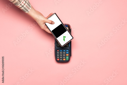 Woman paying by phone on NFC payment contactless terminal on a pink background Canvas
