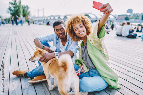 Cheerful african american hipster guys together with dog making selfie photo on front camera of modern smartphone.Positive young man and woman with curly hair shooting video on telephone for blog