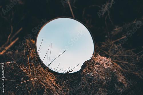 Um  espelho redondo no meio de rochas e plantas a refletir o céu. Canvas-taulu