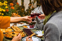 Women Sit At The Festive Autumn Table With Pies And Clink Glasses Of Wine And Laugh. Festive Family Dinner In The Backyard.