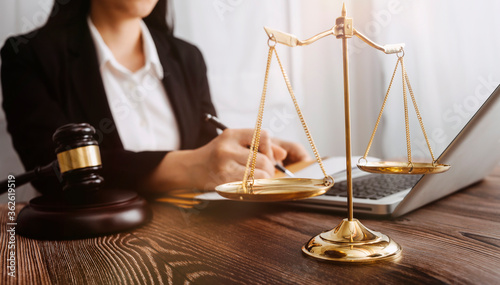 Fototapeta Business and lawyers discussing contract papers with brass scale on desk in office. Law, legal services, advice, justice and law concept picture with film grain effect obraz
