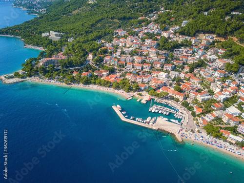 Obraz Amazing aerial view of Makarska riviera, Dalmatia, Croatia. Daytime landscape of popular tourist resort on the Adriatic sea coast at the foot of the rocky Dinara mountains, outdoor travel background - fototapety do salonu