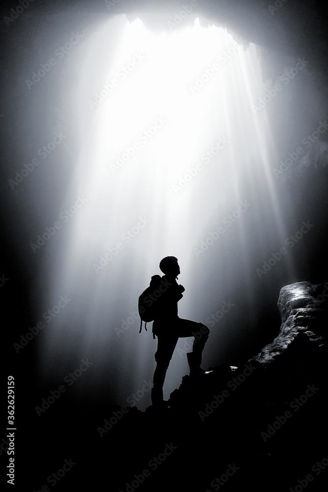 Fototapeta Silhouette Man Standing On Rock Formation Against Bright Sun