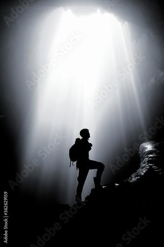 Fototapeta Silhouette Man Standing On Rock Formation Against Bright Sun obraz