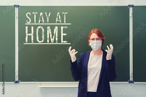 An angry teacher in a medical mask wrote Stay home on the blackboard Canvas-taulu