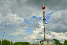 View Of A Very Tall Radio And Internet Tower With Numerous Transmitters And Some Ropes Holding It In Place Located In The Middle Of A Vast Hilltop With A Cloudy Summer Sky Above The Scene