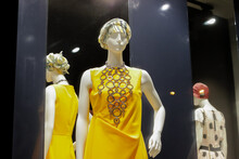 Female Mannequin In Yellow Dress Stands In Window Of Small Modern Boutique Store