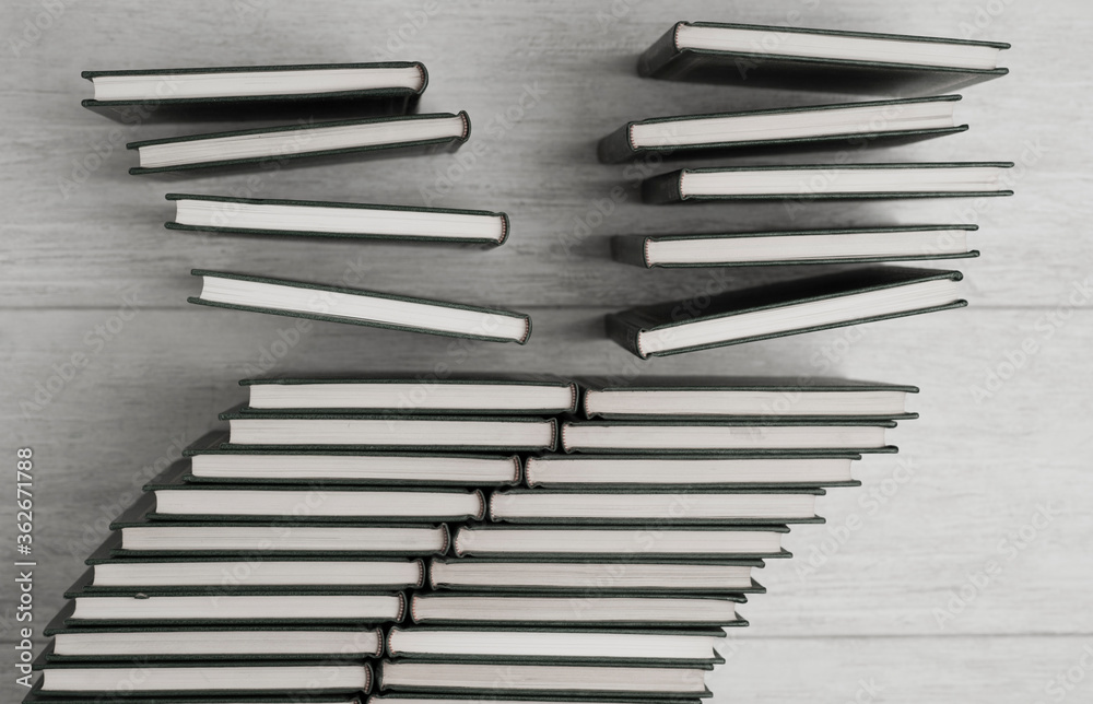Fototapeta books stacked in two columns, books fall in columns of books, black and white, wooden background, top view