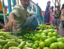 Market Vendor Selling Fruit And Vegetable At Market Stall