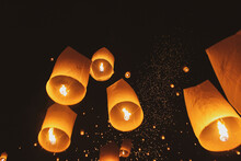 Low Angle View Of Illuminated Paper Lanterns Flying Against Sky At Night