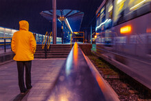 Rear View Of Person On Railroad Station Platform At Night