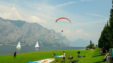 People With Paragliding Equipment By Lake Against Mountain