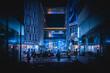 Leinwandbild Motiv People On Illuminated Street Amidst Buildings In City At Night