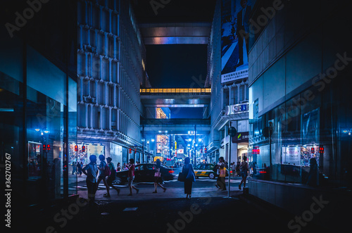 People On Illuminated Street Amidst Buildings In City At Night