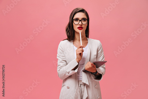 Obraz Beautiful business lady in eyeglasses and modern suit thoughtfully posing with computer tablet on isolated pink background.. - fototapety do salonu