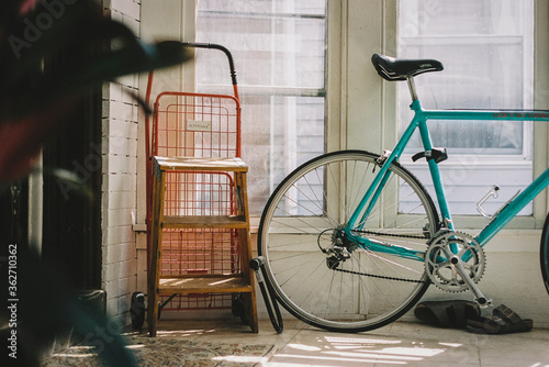 Road bike sits against window inside home on a sunny morning