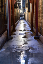 Empty Wet Alley Amidst Buildings At Night
