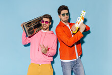 Man In Pink Hoodie And Sunglasses Holds Record Player. Guy In Orange Jacket And Jeans Plays With Water Gun. Friends Have Fun On Blue Background.