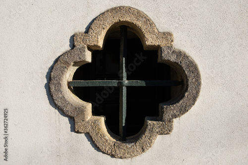 Valokuva Ornate quatrefoil window with iron bars on white wall of old Catholic chapel in